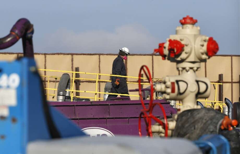 A worker watches over a hydraulic fracturing operation at an Encana  Corp. gas well, near Mead, Colo. In the background is a tall canvas wall around the perimeter of the extraction site, which mitigates noise, light and dust coming from the operation during the drilling and completion phase, which generally takes a few weeks. Photo: Brennan Linsley, AP