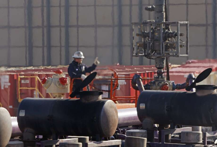 A worker watches over a hydraulic fracturing operation at an Encana  Corp. gas well pad, near Mead, Colo. In the background is a tall canvas wall around the perimeter of the extraction site, which mitigates noise, light and dust coming from the operation during the drilling and completion phase, which generally takes a few weeks. Photo: Brennan Linsley, AP