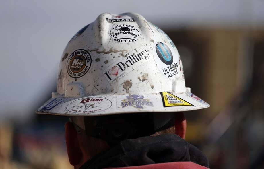 A worker wears a protective helmet decorated with stickers during a hydraulic fracturing operation at a gas well, near Mead, Colo. The first experimental use of hydraulic fracturing was in 1947, and more than 1 million U.S. oil and gas wells have been fracked since, according to the American Petroleum Institute. The National Petroleum Council estimates that up to 80 percent of natural gas wells drilled in the next decade will require hydraulic fracturing. Photo: Brennan Linsley, AP