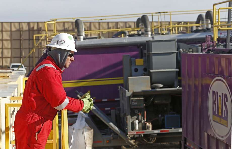 A worker watches over a hydraulic fracturing operation at an Encana  Corp. gas well near Mead, Colo. In the background is a tall canvas wall around the perimeter of the extraction site, which mitigates noise, light and dust coming from the operation during the drilling and completion phase, which generally takes a few weeks. Photo: Brennan Linsley, AP