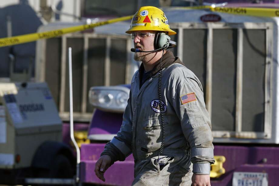 Mike Hamilton, ground and crew supervisor for Bayou Well Services, keeps watch over a hydraulic fracturing operation at an Encana Corp. well pad near Mead, Colo. It takes a few weeks for the half dozen wells on a typical pad to be fracked, after which the petroleum products are extracted for years by operators like Encana. Photo: Brennan Linsley, AP