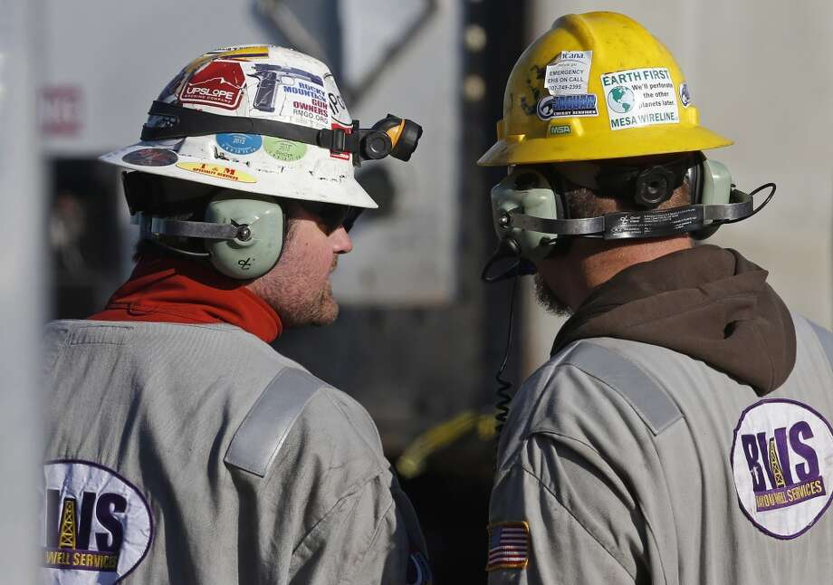 "Workers talk during a hydraulic fracturing operation at an Encana Corp. well pad near Mead, Colo. Hydraulic fracturing, or ""fracking,"" can greatly increase the productivity of an oil or gas well by splitting open rock with water and/or sand pumped underground at high pressure. Photo: Brennan Linsley, AP"