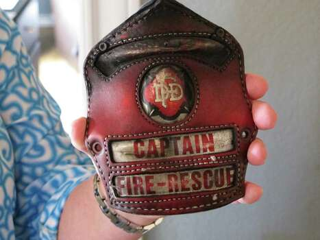 In this April 9, 2014 photo Holly Harris holds a badge that belonged to her husband, Dallas Fire-Rescue Capt. Kenneth Luckey Harris, at her home outside West, Texas. Kenneth Harris was one of 15 people killed in a deadly explosion at West Fertilizer Co., that still raises questions in the community one year later about what happened. (AP Photo/Nomaan Merchant) Photo: Nomaan Merchant, Various (SCC) / AP