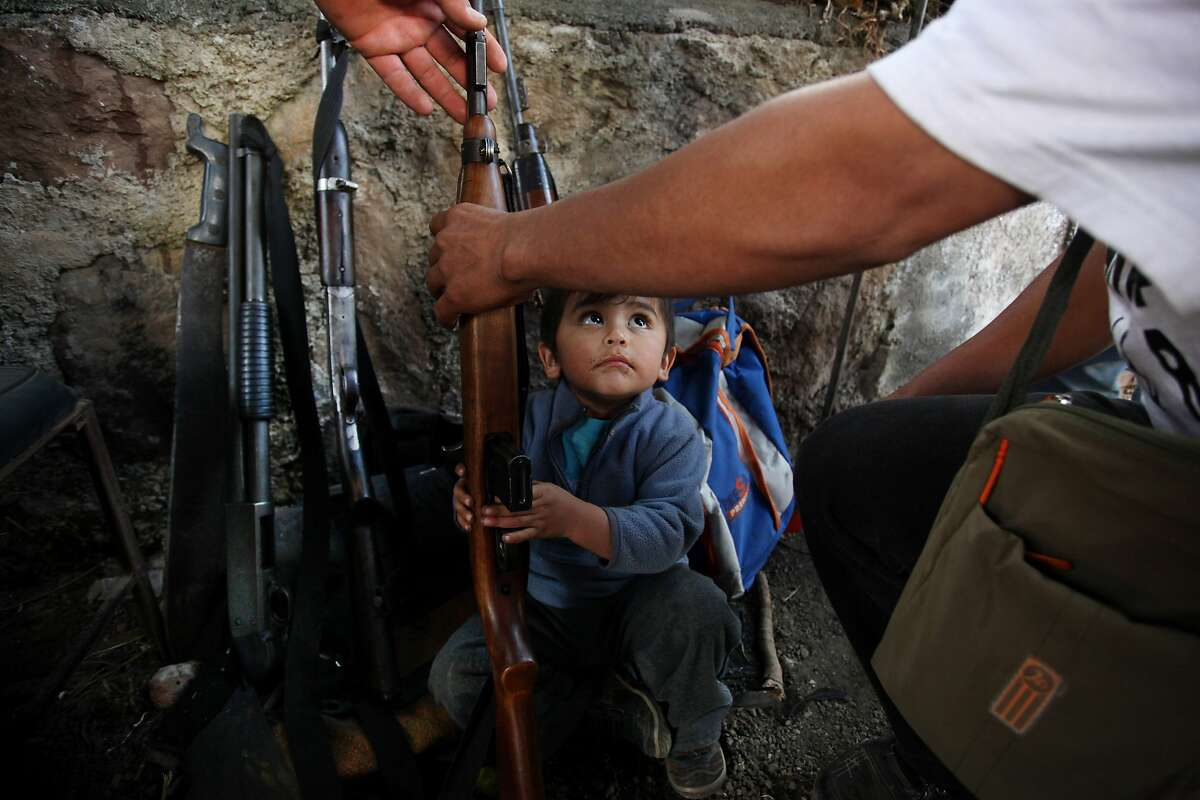 A child looks up as he tries to help his father arrange weapons at a checkpoint of the Self-Defense Council of Michoacan, (CAM), in Tancitaro, Mexico, Thursday, Jan. 16, 2014. Vigilantes in Michoacan state insist they won't lay down their guns until top leaders of a powerful drug cartel are arrested, defying government orders as federal forces try to regain control in a lawless region plagued by armed groups. (AP Photo/Felix Marquez)
