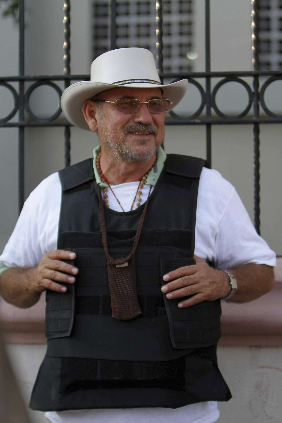 FILE - In this Feb. 9, 2014 file photo, Hipolito Mora, leader of a self-defense movement, wears a bullet proof vest as he stands at the entrance of Apatzingan, in the Michoacan state of Mexico. Self-defense groups in western Mexico are beginning to see internal divisions, amid mutual accusations between Mora and another emerging leader, Luis Antonio Torres, better known as