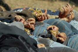 "FILE - In this Dec. 4, 2008, file photo, bodies from a total of 13 bullet-ridden men, with their hands tied behind their backs, victims of the drug war involving Joaquin ""El Chapo"" Guzman's Sinaloa cartel, lie in a field near the town of San Ignacio in the pacific state of Sinaloa, Mexico. Guzman and his cohorts waged an increasingly bloody war over the year with rival gangs. (AP Photo/File)"