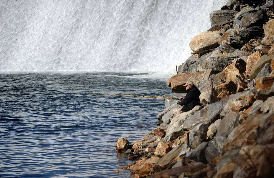 Seth Johnson, of Bridgeport, fishes for striped bass Tuesday, Feb. 21, 2012 at the Derby Dam.  While he hopes to catch a big one, he said if he doesn't then at least he won't have to clean it. Photo: Autumn Driscoll
