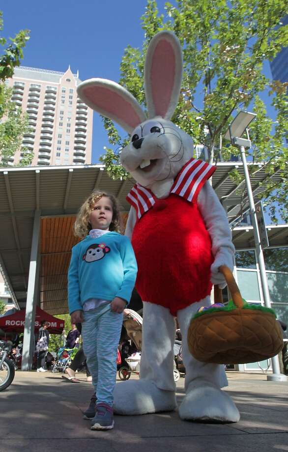 Five-year-old Olivia Henderson takes a photograph with the Easter Bunny during the Easter Arrives Early at Discovery Green Easter Egg Hunt on April 8 in Houston. Photo: James Nielsen, Houston Chronicle