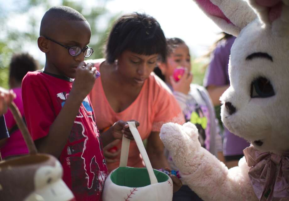Ethan Parker, 10, picks up a candy after turning in his Easter eggs to the Easter bunny after participating on the Lighthouse of Houston 32nd Annual Beeping Easter Egg Hunt for blind and visually impaired children and their families, Saturday, April 12. Photo: Marie D. De Jesus, Houston Chronicle