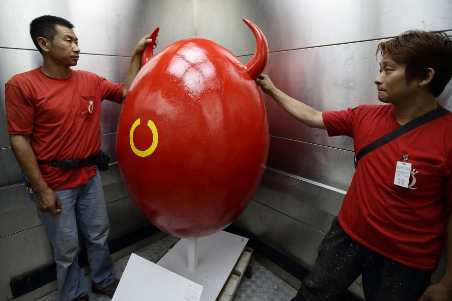 Workers prepare to transport the hand painted giant eggs in Singapore. Spanning across 520 hectares from Mount Faber to the HarbourFront area and onto Sentosa Island, the Great Egg-Venture is set to be the biggest Easter Fiesta to be held in Singapore. Photo: Suhaimi Abdullah, Getty Images