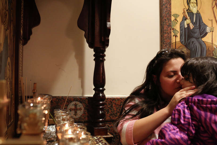"Maria Youssef kisses her daughter, Joymarie Youssef, 2, after they lit a candle for Joymarie's health during Evening Pascha for Holy Week at St. Antony The Great Coptic Orthodox Church in San Antonio on Tuesday, April 15, 2014. Joymarie had been sick with a 104 degree fever last week. ""I'm just praying that God heals her completely,"" Maria said. Photo: Lisa Krantz, SAN ANTONIO EXPRESS-NEWS / SAN ANTONIO EXPRESS-NEWS"