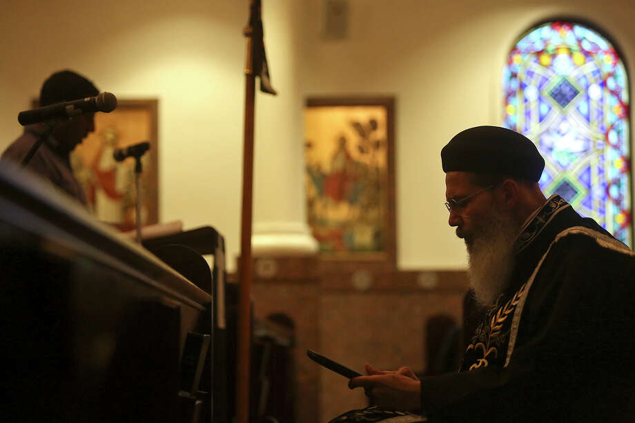 Father Makary Ibrahim, right, sits as a parishioner reads during Evening Pascha for Holy Week at St. Antony The Great Coptic Orthodox Church in San Antonio on Tuesday, April 15, 2014. Photo: Lisa Krantz, SAN ANTONIO EXPRESS-NEWS / SAN ANTONIO EXPRESS-NEWS