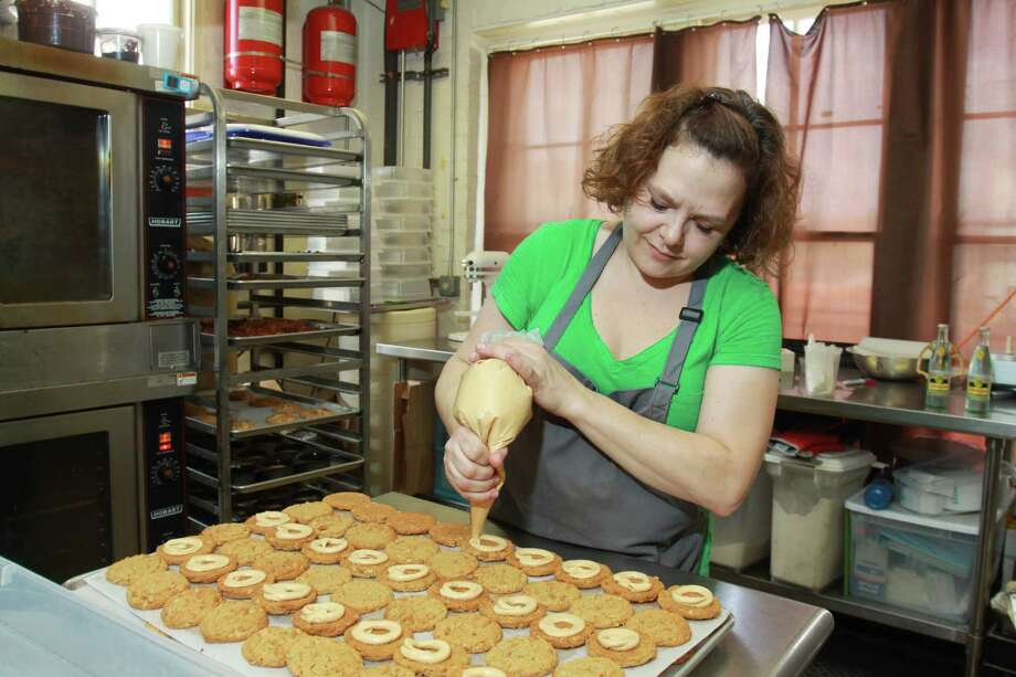 (For the Chronicle/Gary Fountain, April 12, 2014) Fluff Bake Bar pastry girl/owner Rebecca Masson finishing Fluffernutters in her current baking location. This is the entire space where last year she baked approximately 45,000 sweets on this eight-foot table. Rebecca recently complete a Kickstarter fund to get her own bakery space, and is working on getting a larger space and opening a retail bakery and dessert bar. Photo: Gary Fountain, Freelance / Copyright 2014 by Gary Fountain