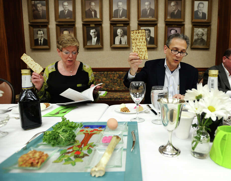 Sherry Horwitz, left, and Rabbi Joshua Taub read a blessing while holding a piece of matzo, unleavened bread, during Tuesday night's Seder meal. During Passover, observers cannot eat leavened bread. Temple Emanuel Beaumont held its second night of Passover Seder meals on Tuesday night. During Seder, the story of the Exodus from Egypt is told and foods representative of the story's retelling are served.