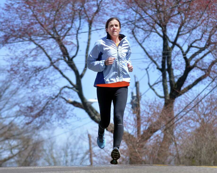 Sally Duval runs near her home in Greenwich, Thursday, April 17, 2014. Duval will be running in the Boston Marathon on Monday to make a statement against evil.  Duval's husband ran in the Boston Marathon last year and was close to the finish line when the terrorist's bombs exploded. Duval lost her brother, Teddy Maloney, in the terrorist attacks on the World Trade Center in New York City on 9/11. Photo: Bob Luckey / Greenwich Time