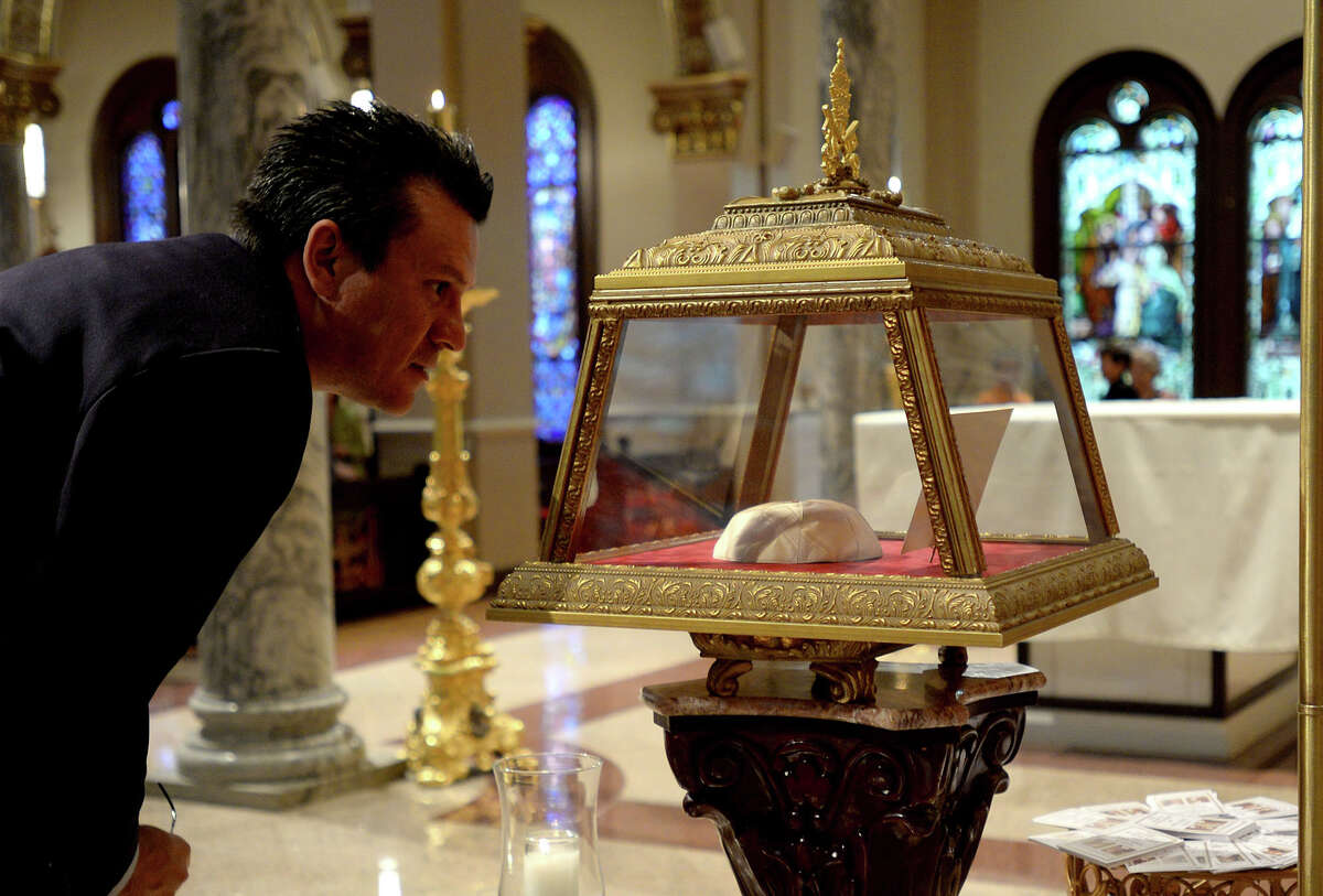 Jesus Abrego looks over the skull cap 'zucchetto' worn by Saint John XXII during his papacy after a service Thursday to unveil the relic at St. Anthony Cathedral Basilica. Born as Angelo Giuseppe Roncalli and served as pope from October 1958 to his death in 1963. Photo taken Thursday, April 17, 2014 Guiseppe Barranco/@spotnewsshooter