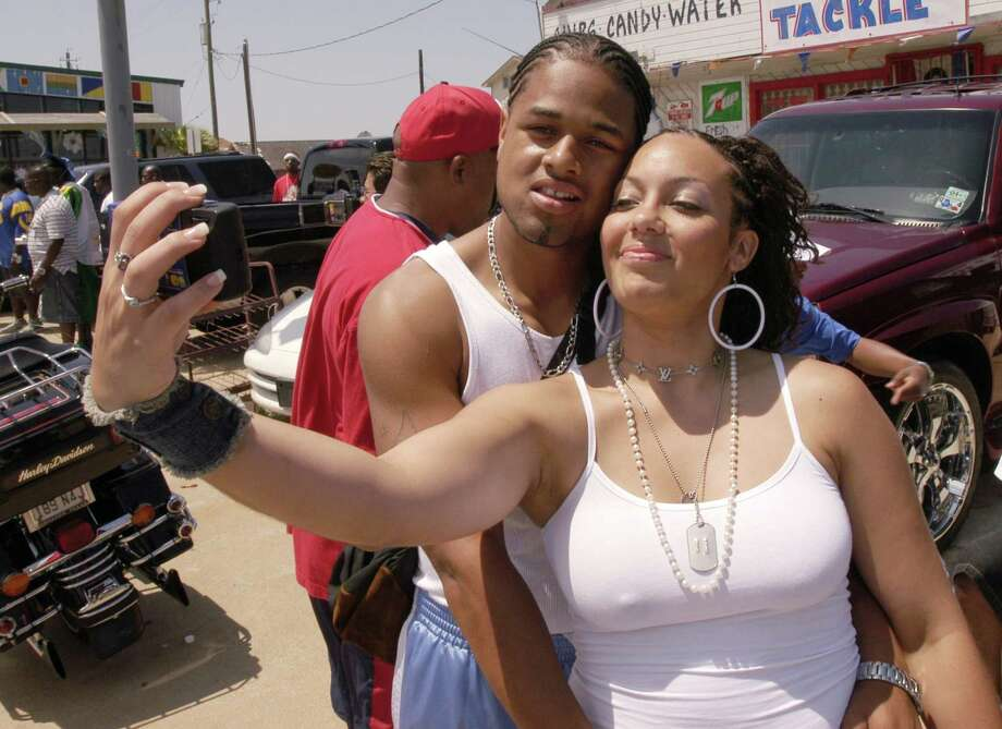 Whitney Gross from Dallas takes her picture with Maurice Davis from Los Angeles on Seawall Blvd. during  Beach Party Weekend in Galveston Saturday April 17,2004. Photo: Dave Rossman, For The Chronicle / Freelance