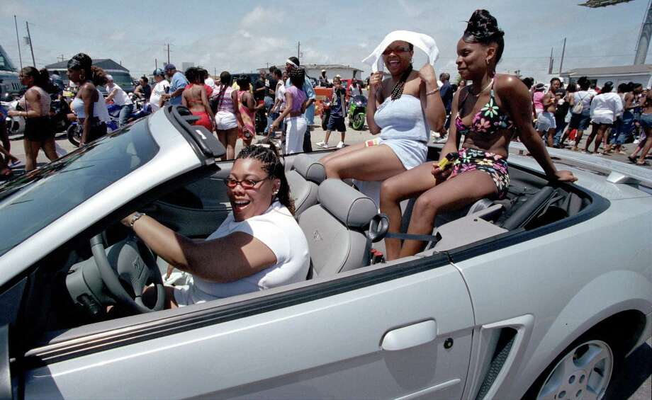 Porshia Wilson (driving), Jasmine Dean (R) and Shakera Bankston (towel on head) make their way along the seawall Saturday afternoon during the early hours of the Beach Party 2002 held in Galveston.  Crowds were smaller than in years past but growing as the day wore on.  Police said that there had been no incidents or trouble from the revelers. Photo: Karl Stolleis, Houston Chronicle / Houston Chronicle