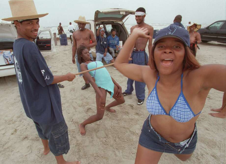 An angry reveler from Dallas partying Sunday afternoon March 22, 2001 on Galveston's East Beach during Beach Party Weekend raises her hand and rushes the photographer as she yells that there will be no photographs taken of her group of friends without paying two dollars first. The women attending the annual event sometimes require payment of a dollar or two before allowing themselves to be photographed. Photo: D. Fahleson, Special To The Chronicle / Freelance