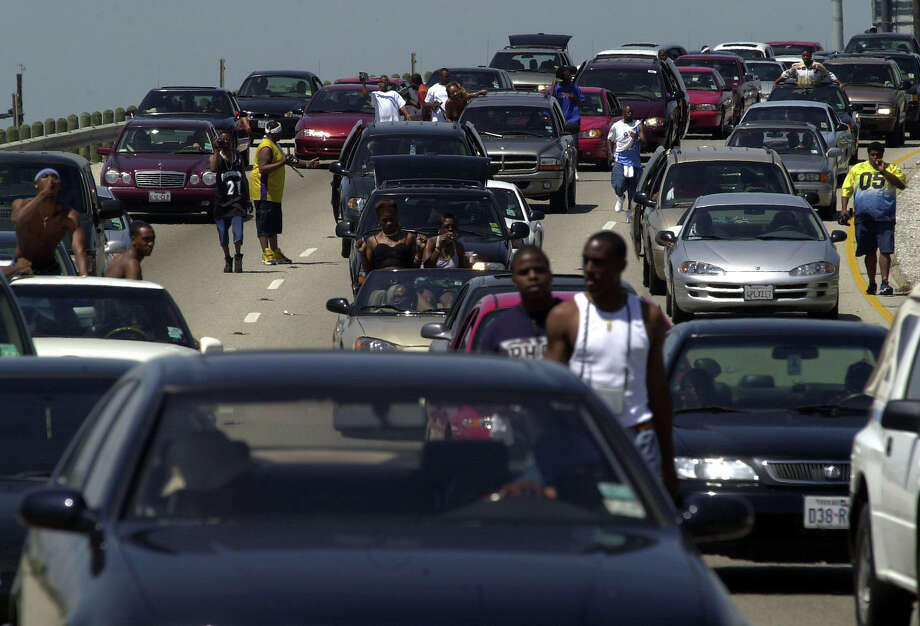 Party goers take a stroll down I-45 as traffic slows to a crawl Saturday,  April 21, 2001 in Galveston. Thousands people flocked to Galveston to be a part of Beach Party 2001. Galveston officials say there could be 200,000 visitors on the island to participate in the festivities. Photo: CHRISTOBAL PEREZ, HOUSTON CHRONICLE / HOUSTON CHRONICLE