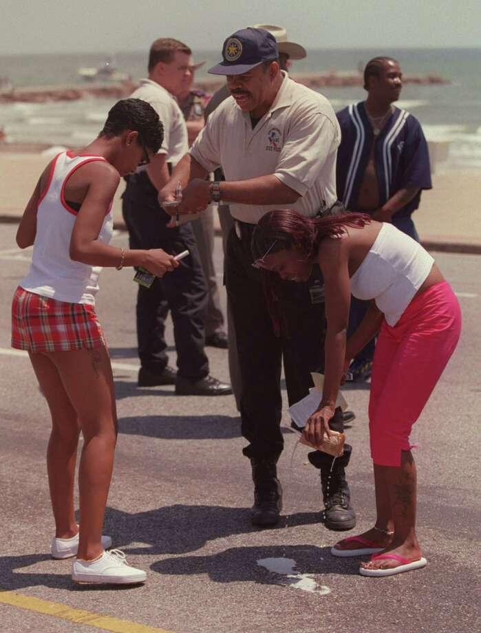 Texas Alcoholic Beverage Commission  Officer  Chad Chadwick, in baseball cap, makes this woman empty her beer onto Seawall Drive during Beach Party Weekend 2000 in Galveston Saturday April 15, 2000, with her friend looking on. Photo: Andrew Innerarity, Houston Chronicle / Houston Chronicle
