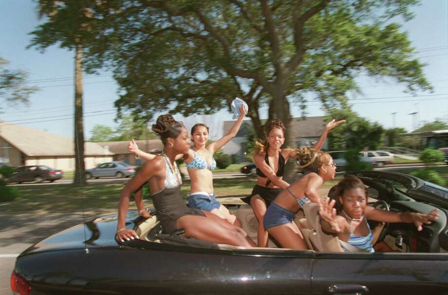 A carload of young women wave as they make their way down Galveston's Broadway Saturday for the Beach Party Weekend. Streets carried bumper-to-bumper traffic as thousands of students from colleges across the Southeast flocked to the city for the annual event. Photo: Kevin Fujii, HOUSTON CHRONICLE / HOUSTON CHRONICLE