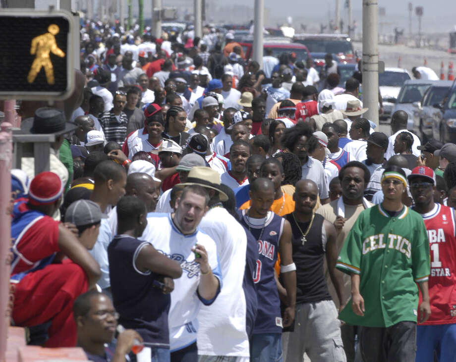 Crowds walk along Seawall Blvd. at Beach Party Weekend in Galveston Saturday April 17,2004. Photo: Dave Rossman, For The Chronicle / Freelance
