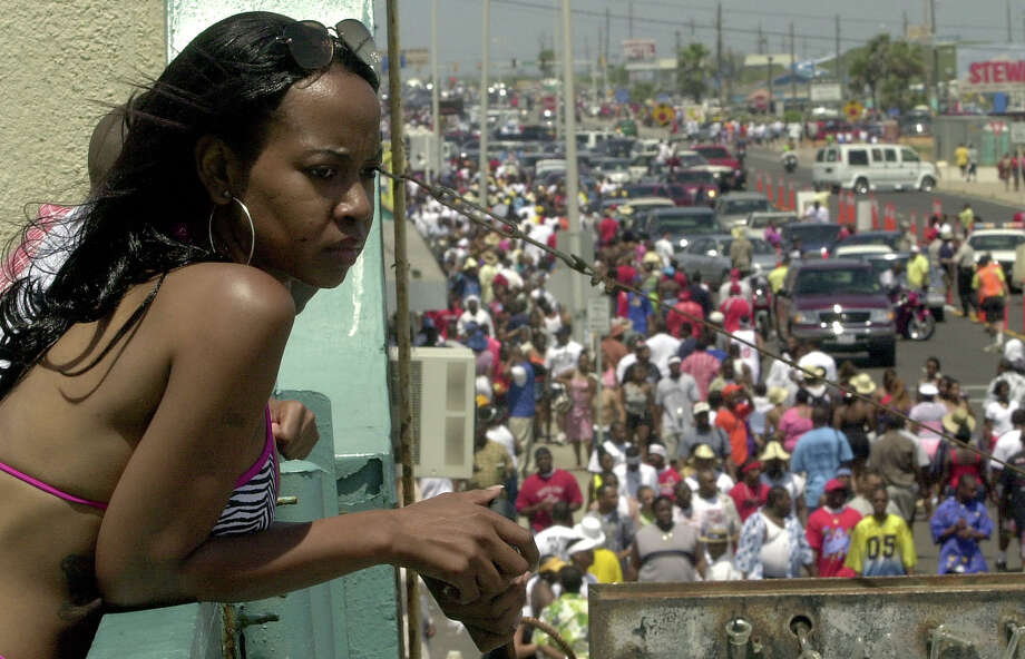 Chenea Dent of Houston looks over the balcony of the Mayflower Inn  to watch people walk down Galveston's seawall participating in Beach Party weekend, Saturday,  April 21, 2001 in Galveston. Galveston officials say there could be 200,000 visitors on the island to participate in the festivities. Photo: CHRISTOBAL PEREZ, HOUSTON CHRONICLE / HOUSTON CHRONICLE