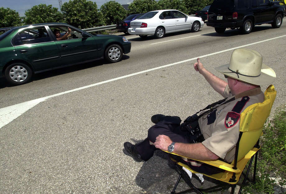 Constable George Loner, precint four, gives the thumbs up to party goers as traffic slows to a crawl on I-45 Saturday,  April 21, 2001 in Galveston. 'They are just here to have fun ,' said Constable Loner. Thousands people flocked to Galveston to be a part of Beach Party 2001. Galveston officials say there could be 200,000 visitors on the island to participate in the festivities. Photo: CHRISTOBAL PEREZ, HOUSTON CHRONICLE / HOUSTON CHRONICLE
