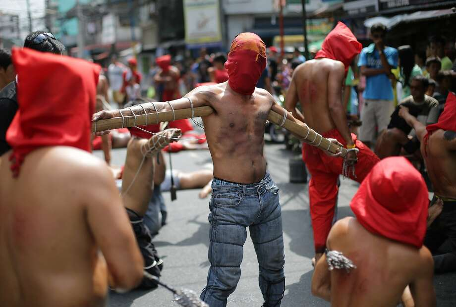 Instead of flogging themselves,some Filipino penitents imitate Christ on the cross by having their arms lashed to splints perpendicular to their bodies. (Mandaluyong, Philippines.) Photo: Aaron Favila, Associated Press