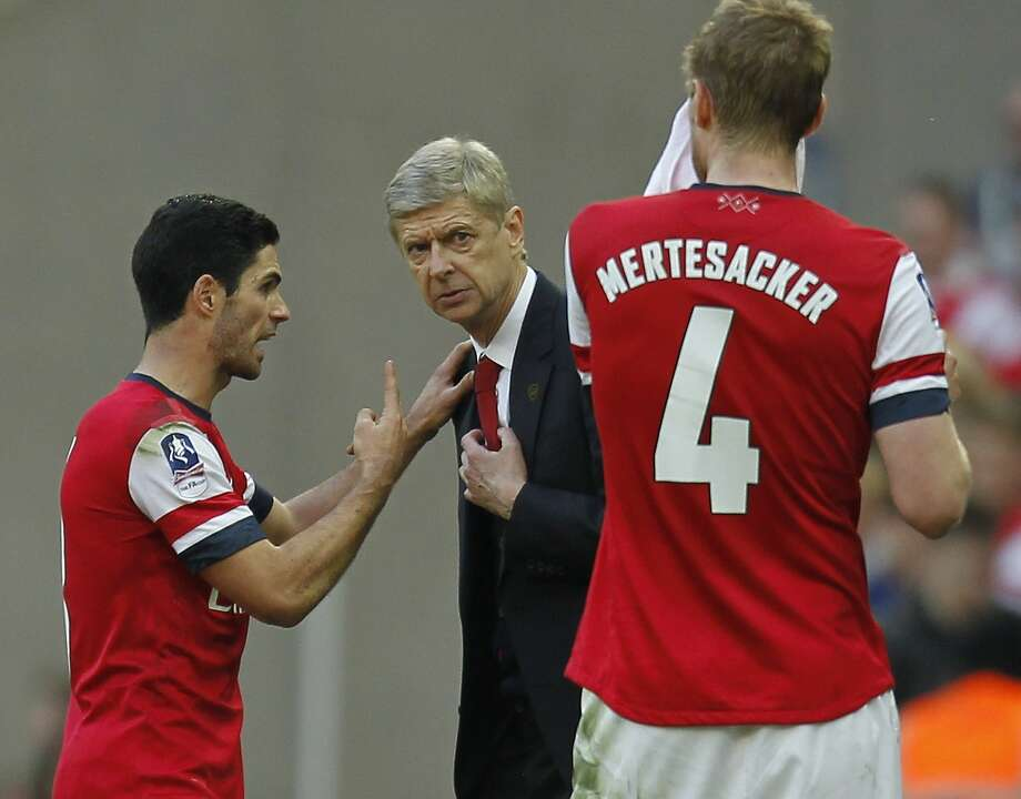 Arsenal's French manager Arsene Wenger can talk to Spanish-born midfielder Mikel Arteta (left) and German-born defender Per Mertesacker in their native languages. Photo: Ian Kington, AFP/Getty Images