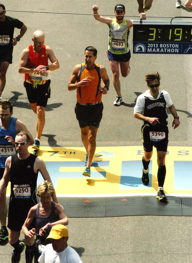 Randy Chamberland of Shelton (with bib number 5390) and Brian Hennessey (no bib) formerly of Newtown, cross the finish line in last year's Boston Marathon. Photo: Contributed Photo / Connecticut Post Contributed
