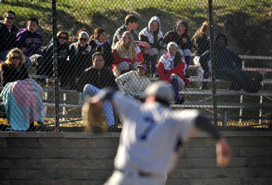 Fans watch from the stands as Wilton's Trevor Blond pitches during the Warriors' baseball game against Westhill at Westhill High School in Stamford, Conn., on Wednesday, April 16, 2014. Westhill won, 9-0. Photo: Jason Rearick / Stamford Advocate