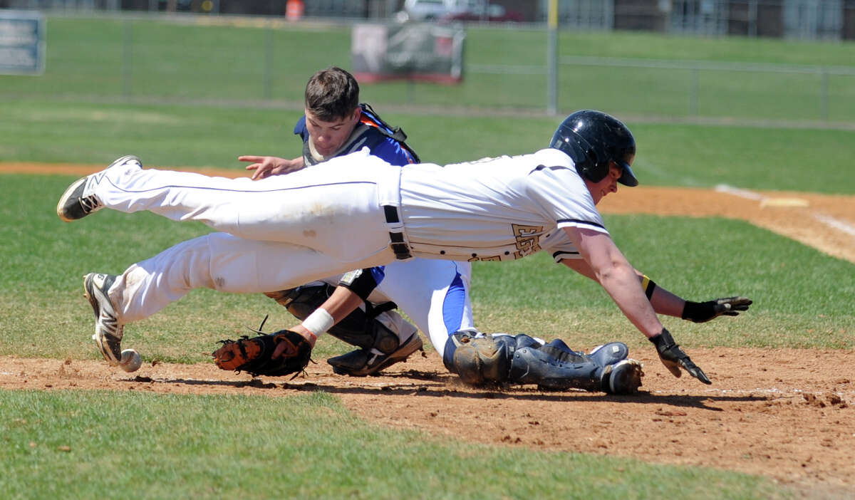 Trumbull's Zach Sagar dives for home plate as Danbury catcher Michael Schweitzer loses hold of the ball during their game Thursday, April 17, 2014, at Trumbull High in Trumbull, Conn.