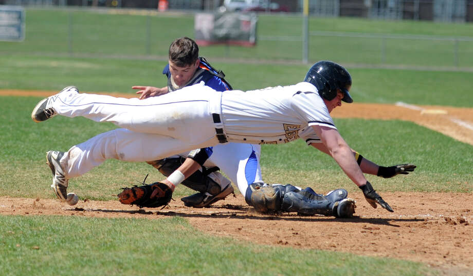 Trumbull's Zach Sagar dives for home plate as Danbury catcher Michael Schweitzer loses hold of the ball during their game Thursday, April 17, 2014, at Trumbull High in Trumbull, Conn. Photo: Autumn Driscoll / Connecticut Post