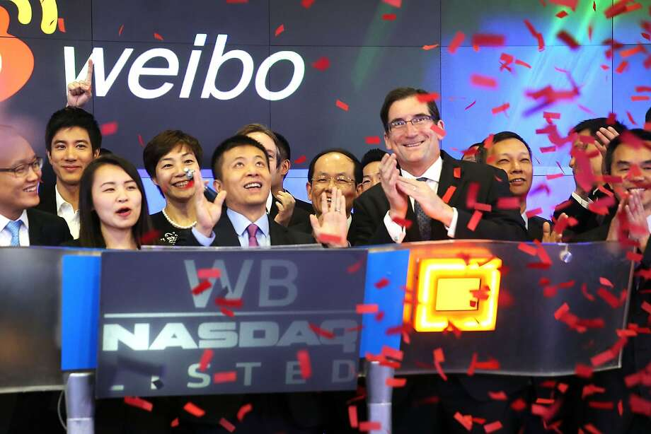 Weibo CEO Charles Chao (center) opens the trading day on the Nasdaq exchange. The Chinese Twitter-like service began trading Thursday. Photo: Spencer Platt, Getty Images