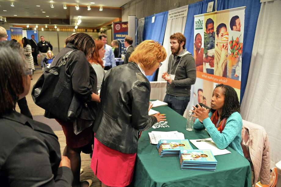 Job seekers queue up at the Whole Foods recruiting booth manned by pay and benefit specialists Josh Williams and Tami Garvin, right, during the Martin Luther King Job Fair Thursday afternoon, April 17, 2014, at Empire State Plaza Convention Center in Albany, N.Y.  (John Carl D'Annibale / Times Union) Photo: John Carl D'Annibale / 00026509A