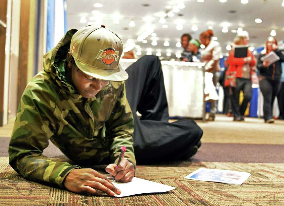 Jawaun Daniels of Albany fills out a job application during the Martin Luther King Job Fair Thursday afternoon, April 17, 2014, at Empire State Plaza Convention Center in Albany, N.Y.  (John Carl D'Annibale / Times Union) Photo: John Carl D'Annibale / 00026509A