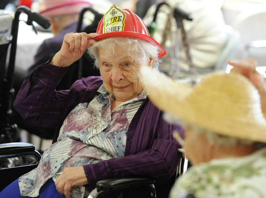 Carolyn Merritt, of Danbury, adjusts her firefighter's hat during the Hat Day Celebration at the Filosa Hancock Hall in Danbury, Conn. Thursday, April 17, 2014.  Photo: Tyler Sizemore / The News-Times