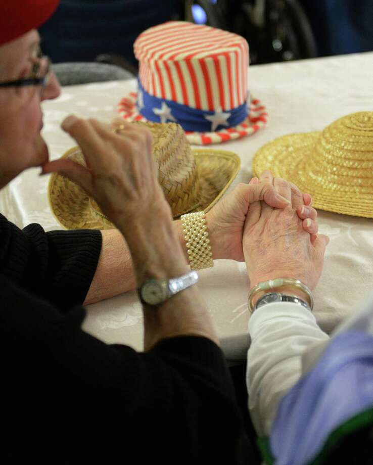 Gloria and Bill Keenan, of Danbury, hold hands during the Hat Day Celebration at the Filosa Hancock Hall in Danbury, Conn. Thursday, April 17, 2014. Members of the Danbury Museum spoke with the crowd about the history of Hat City.  Photo: Tyler Sizemore / The News-Times