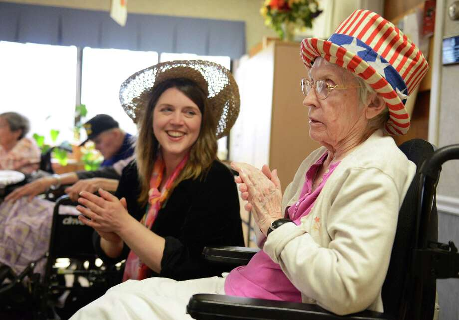 Certified Therapeutic Recreation Specialist Holly Taylor-Fry, left, and Mary Salvato, of Danbury, clap along to music during the Hat Day Celebration at the Filosa Hancock Hall in Danbury, Conn. Thursday, April 17, 2014.  Photo: Tyler Sizemore / The News-Times