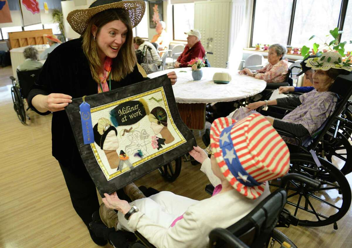 Certified Therapeutic Recreation Specialist Holly Taylor-Fry shows hat-related art to Mary Salvato, of Danbury, during the Hat Day Celebration at the Filosa Hancock Hall in Danbury, Conn. Thursday, April 17, 2014. Members of the Danbury Museum spoke with the crowd about the history of Hat City.