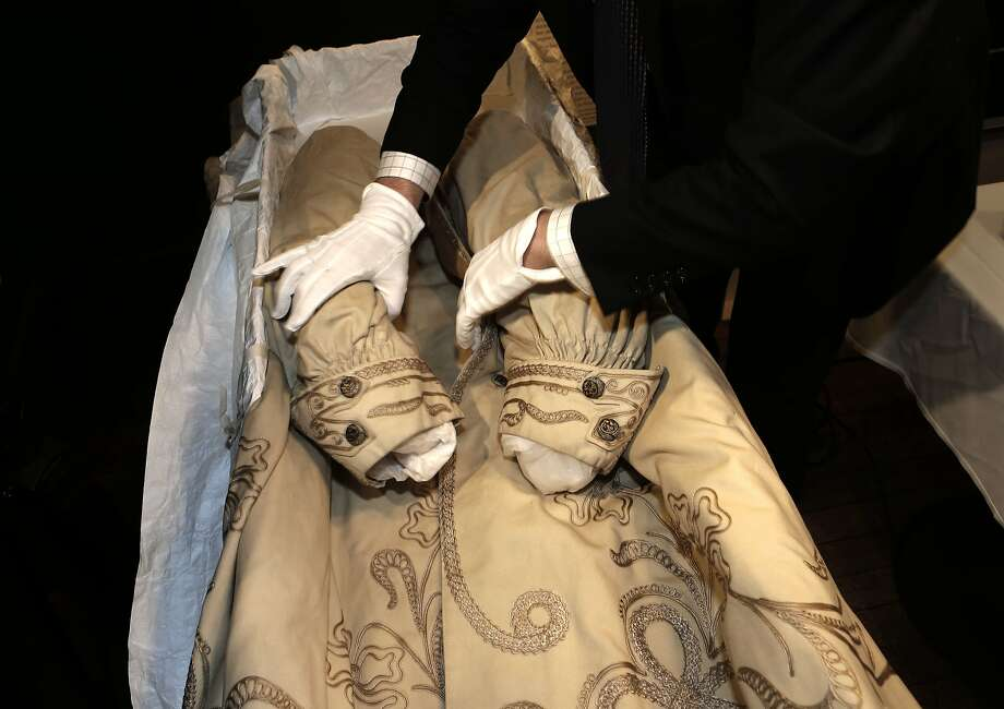 Fashion historian Kevin Jones wears gloves while unpacking the ornate coat from 1906. Photo: Michael Macor, The Chronicle