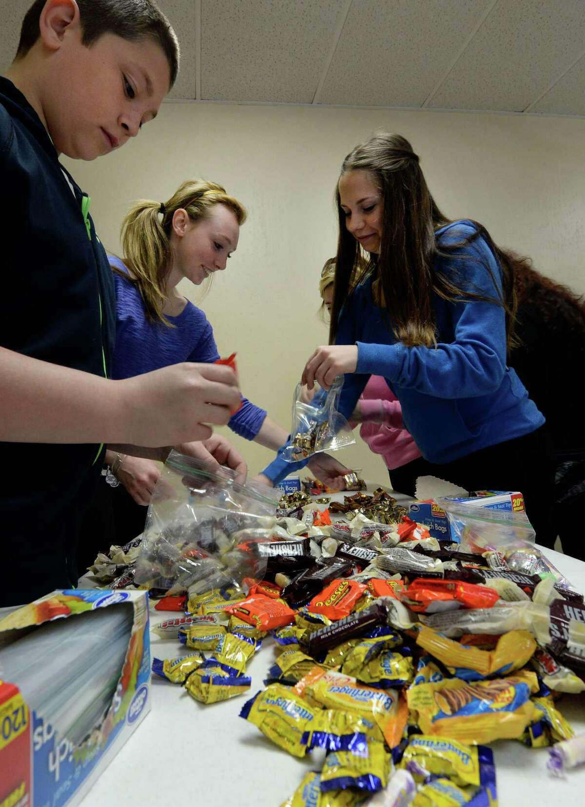 Joe Leichenauer, 12, of Stephentown, left, Christie Cullum,15, of East Greenbush, center, and Alexis Charland, 15, of East Greenbush assemble gift bags full of candy Thursday morning, April 17, 2014, in preparation for the Easter Sunday celebration to take place at the Albany City Mission in Albany, N.Y. (Skip Dickstein / Times Union)