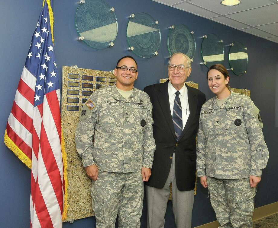 Pictured left to right are Sgt. Marcial Sepulveda, Texas Army National Guard; D.A. Buell, U.S. Navy and Air Force veteran; and Spc. Leah Newman, Texas Army National Guard stop for a photo next to the Wall of Honor inside the Central campus Center of Excellence for Veteran Student Success.