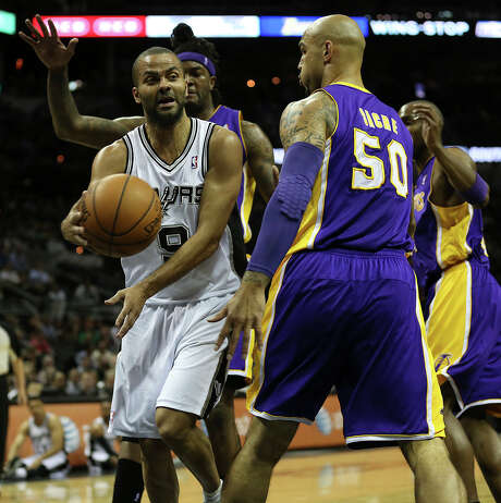 San Antonio Spurs' Tony Parker passes around Los Angeles Lakers' Robert Sacre during the first half at the AT&T Center, Wednesday, April 16, 2014. Photo: San Antonio Express-News / ©2014 San Antonio Express-News