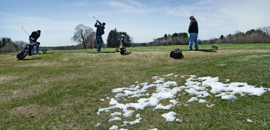 With snow still evident, Tom Conti, left, Billy Comtois, center, and Mike McCarthy, right, get some practice on the driving range at Capital Hills at Albany municipal golf course Thursday afternoon April 17, 2014, in Albany, N.Y. The course opened for the season on Thursday. (Skip Dickstein / Times Union) Photo: SKIP DICKSTEIN