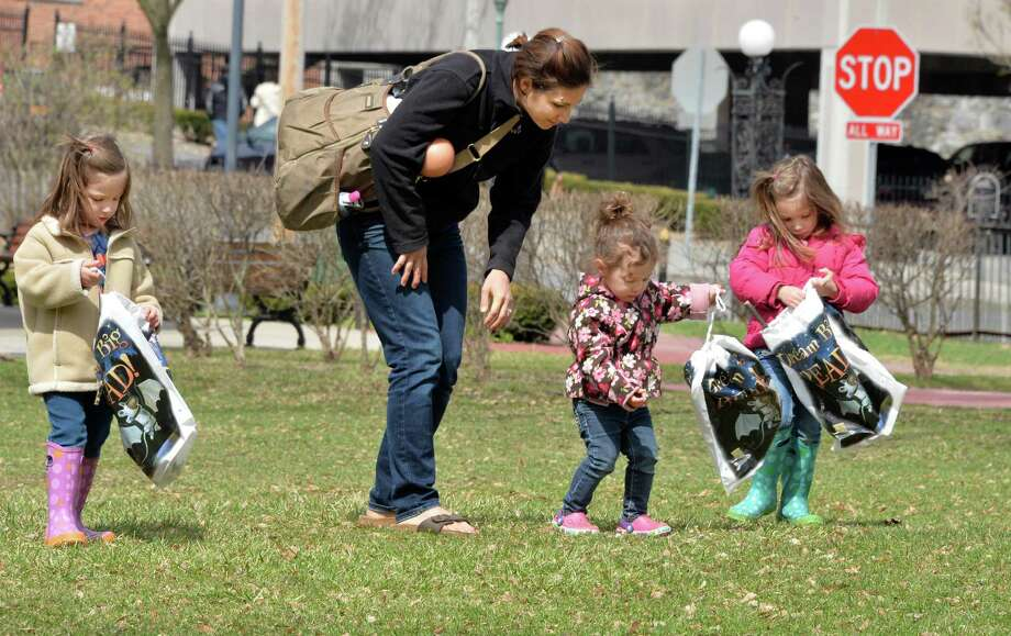 Jessica Bizzarro of Wilton helps daughters Alessandra, 3, left, Julianna, 2, center, and Gabriella, 3, right, collect natural materials in Congress Park to make a twig vase during a Reconnecting with Nature program held by Saratoga Springs Public Library Thursday morning, April 17, 2014, in Saratoga Springs, N.Y.  (John Carl D'Annibale / Times Union) Photo: John Carl D'Annibale / 00026521A