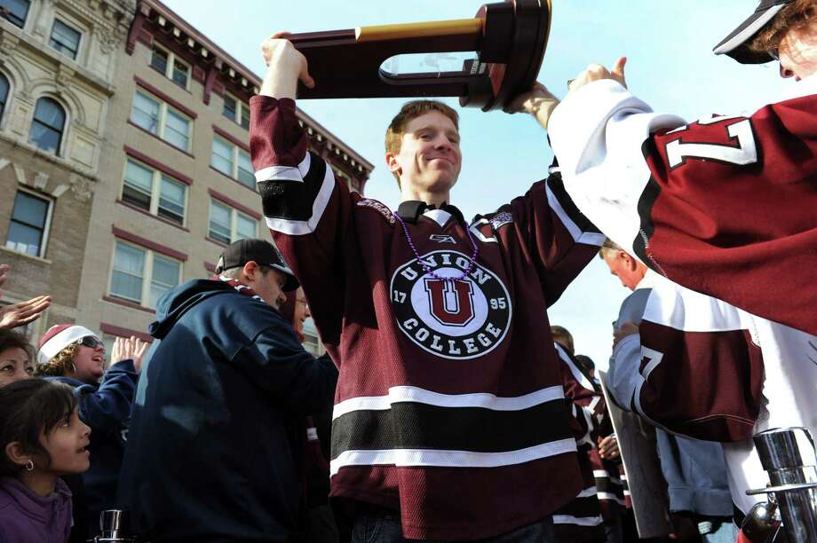 Union's Mat Bodie, center, carries the NCAA Hockey Championship trophy through the sea of fans during a celebration to mark the team's achievement on Thursday, April 17, 2014, at City Hall in Schenectady, N.Y. (Cindy Schultz / Times Union) Photo: Cindy Schultz / 00026500A