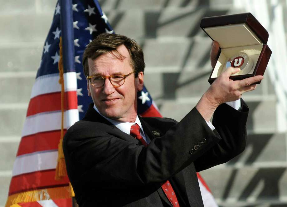 Union's president Stephen C. Ainlay raises a diamond-encrusted puck from Northeastern Fine Jewelry to honor the college's NCAA Hockey Championship on Thursday, April 17, 2014, at City Hall in Schenectady, N.Y. (Cindy Schultz / Times Union) Photo: Cindy Schultz / 00026500A